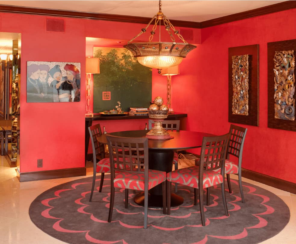 Red dining room decorated with gorgeous wall arts and a brass chandelier that hung over the wooden dining set sitting on a round area rug.