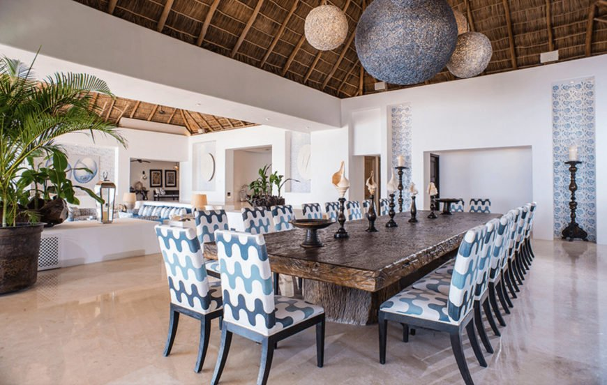 Oversized round weaved pendants illuminate this open dining room featuring an immense tree dining table accented with patterned chairs that complement with the inset wall niches.
