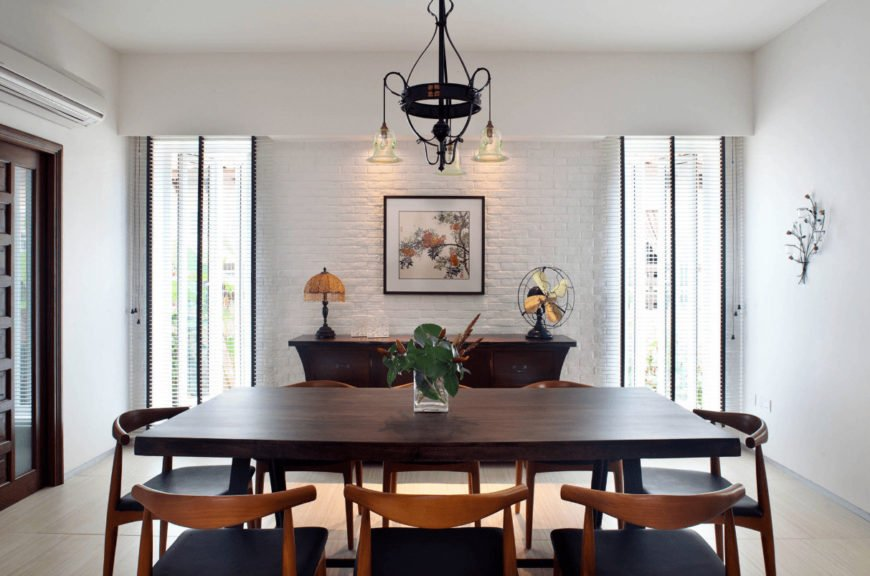 Airy dining room offers a wooden dining set and buffet table topped with a lampshade and fan. It is accented with a charming art piece mounted on the white brick wall.