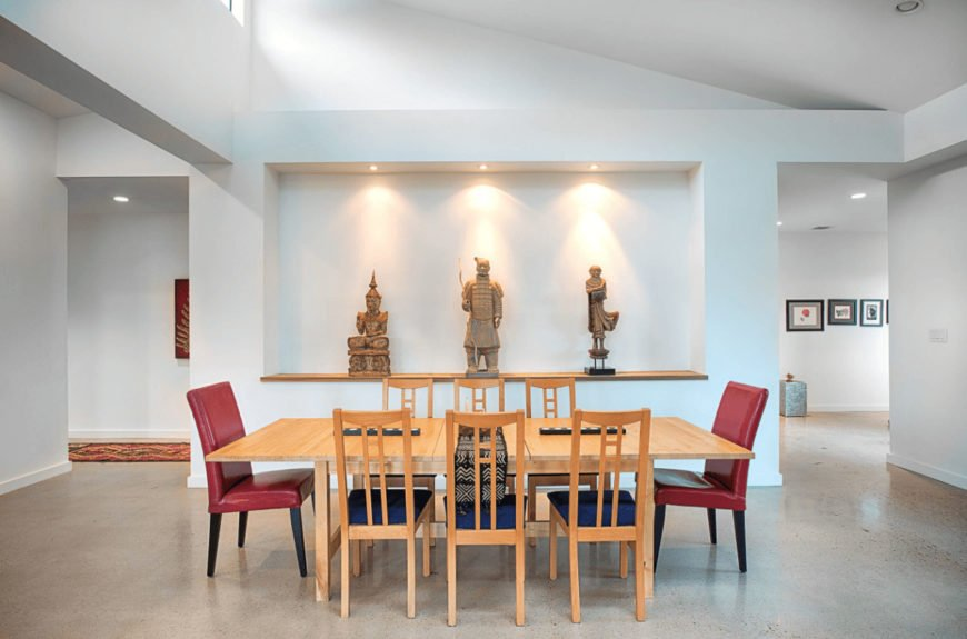 Red high back chairs stand out in this white dining room with light wood dining set and an inset wall filled with Asian sculptures.