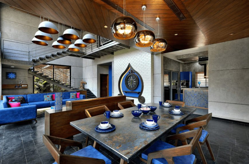 Open dining room with a pop of blue color from the dinnerware and cushioned chairs surrounding the rustic dining table. It has limestone flooring and chevron wood ceiling with hanging high gloss brass pendants.