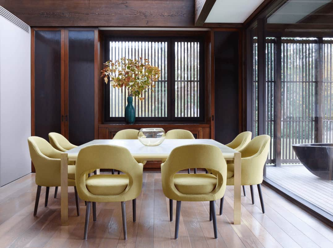 Cozy dining room showcases yellow round back chairs and a wooden dining table topped with a glass bowl. It includes built-in storage by the glazed window accented with a lovely flower vase.