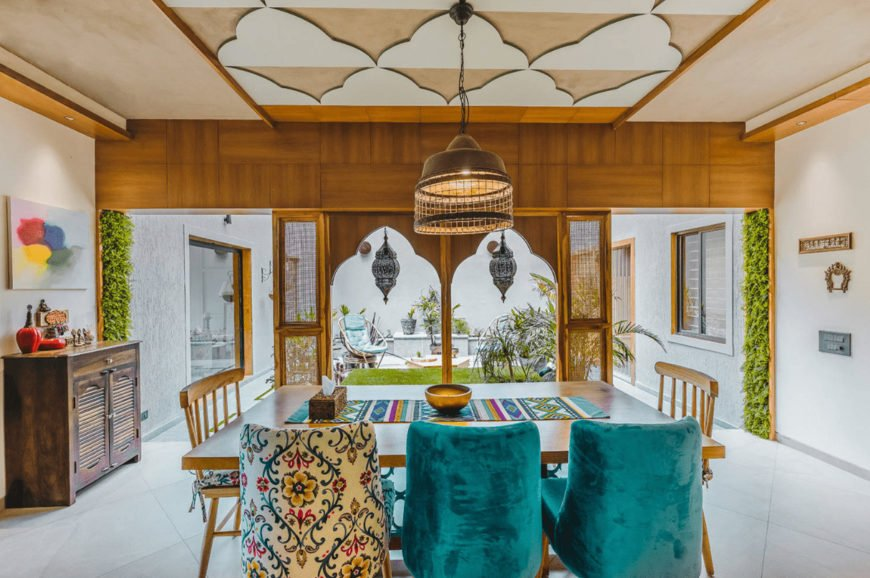 A caged pendant light that hung from the stylish ceiling illuminates this Asian dining room featuring a wooden table that's lined with a colorful runner and paired with mismatched chairs.
