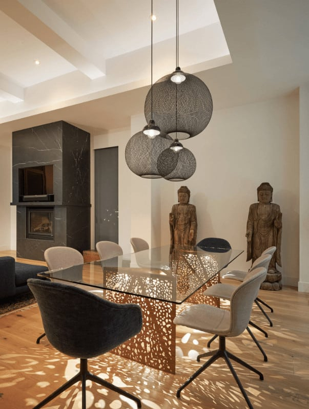 A pair of Buddha sculptures stand in front of the glass top table and round back chairs in this dining room illuminated by spherical pendants that hung from the tray ceiling.