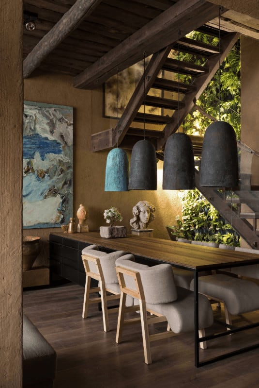 A rustic Asian dining room lighted by dome pendants that hung over the wooden dining set accented with various decors and a living green wall.