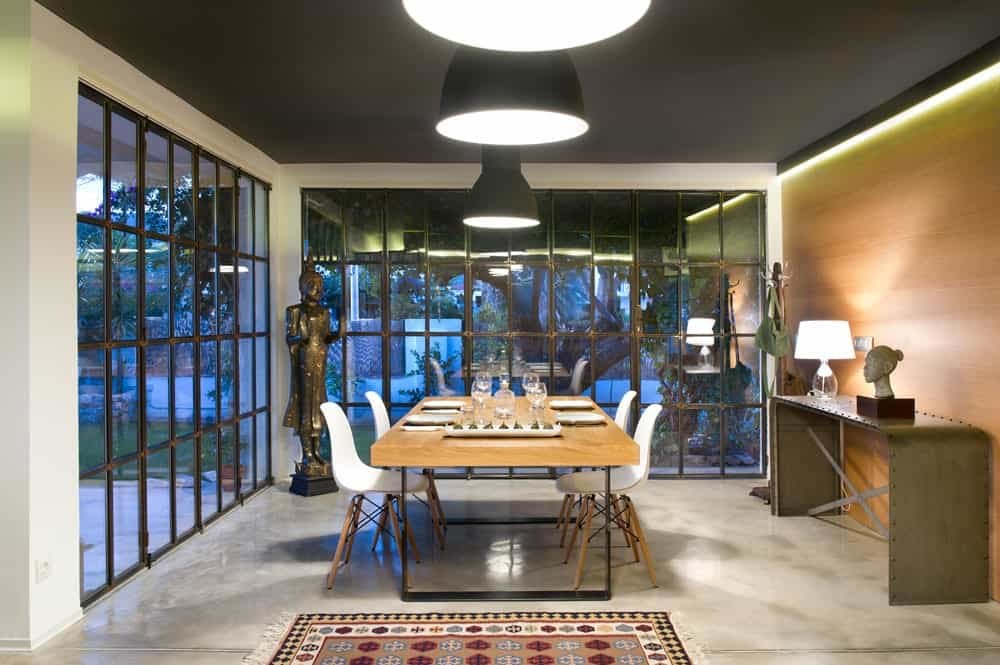 Asian dining room with full height glazing and concrete flooring topped by a bordered area rug. It has a wooden dining table and white modern chairs guarded by a Buddha sculpture on the side.