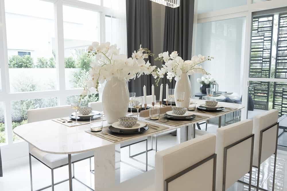 Bright dining room features a sleek white dining set accented with lovely flowers. It is situated against the glass paneled windows which bring plenty of natural light in.