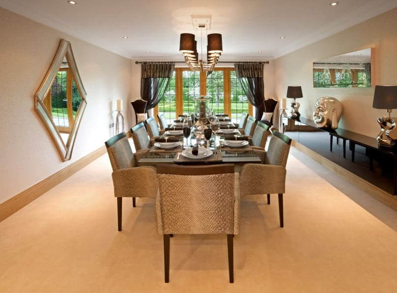 Luxury dining room designed with a diamond mirror along with chrome head decor and lamps that sit on a floating cabinet. It has an elegant dining set and wooden framed windows overlooking the lush green outdoor.