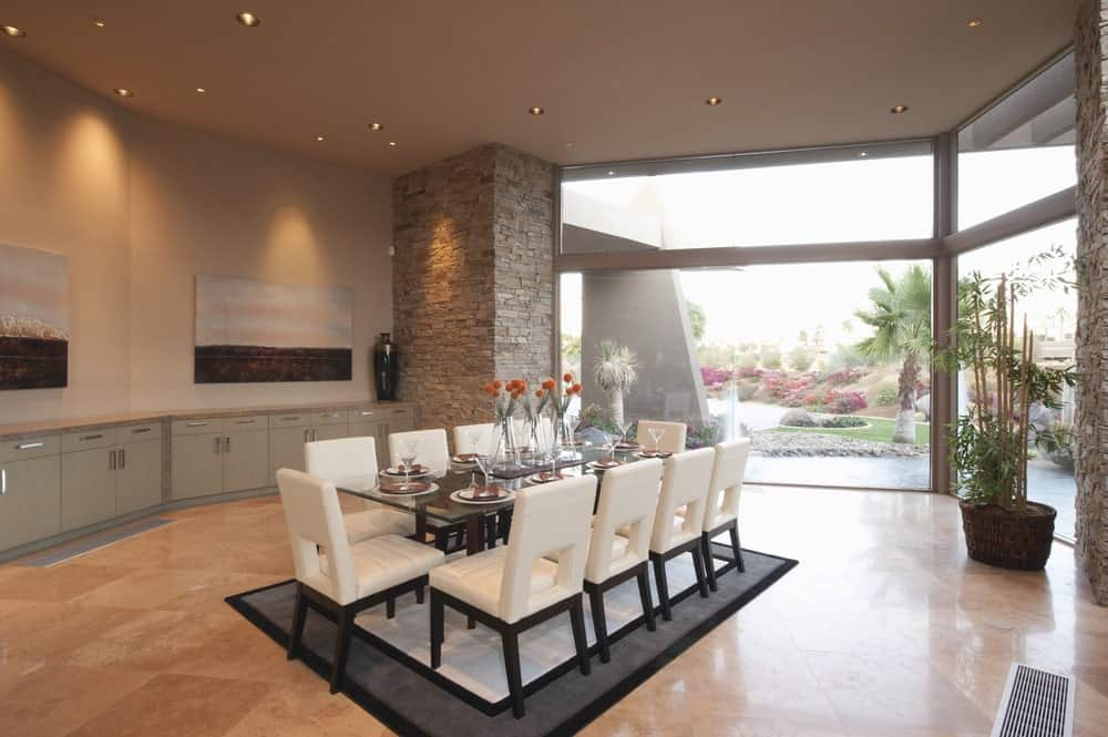 Spacious dining room with beige tiled flooring and panoramic windows overlooking the majestic garden. It has a glass top dining table surrounded with white modern chairs on a gray bordered rug.