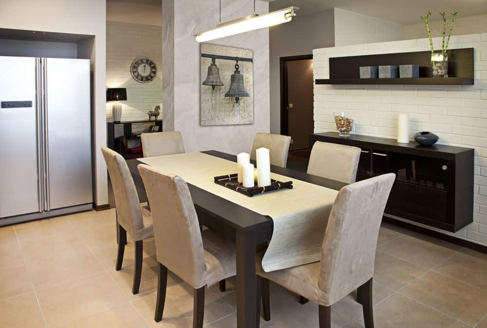 A linear pendant light hangs over the dark wood table in this Asian dining room showcasing beige velvet chairs along with floating storage and shelf mounted on the white brick wall.