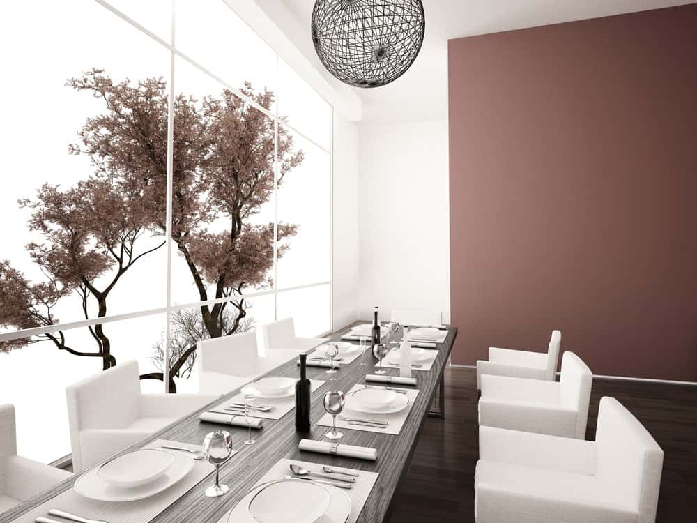 A modern Asian dining room with sleek white chairs and a wooden dining table that complements with the hardwood flooring lighted by a string woven sphere pendant.