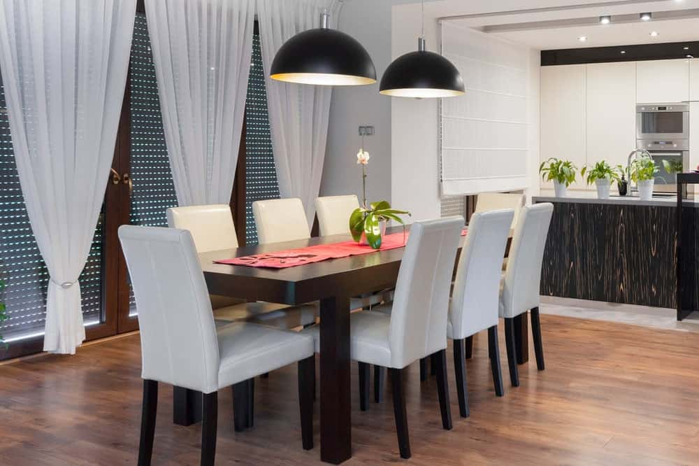 Cozy dining room with dark wood dining table and white leather chairs contrasted by black dome pendants. It has hardwood flooring and full height windows dressed in sheer curtains.