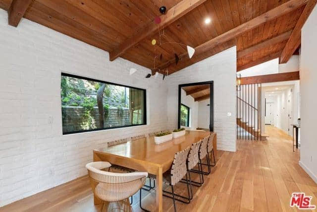 This simple dining room has a wooden shed ceiling with exposed wooden beams that hangs a decorative geometric art piece over the long wooden dining table that matches the hardwood flooring that complements the white textured walls.