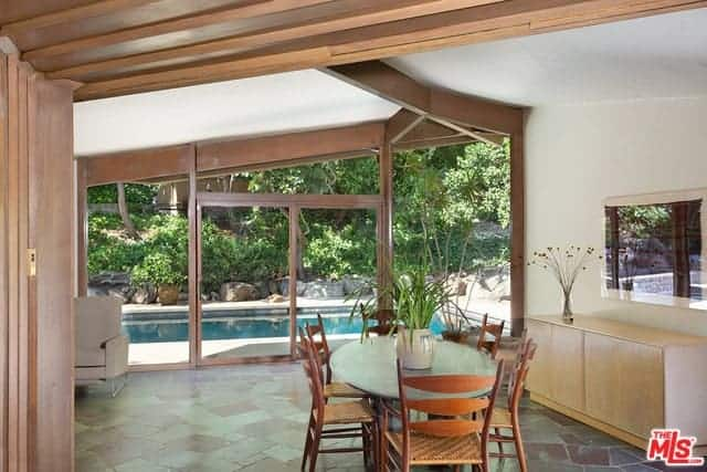 This informal dining area has a flooring made of a mosaic of various gray and terracotta tiles that works well with the natural lights coming in from the glass doors that lead to the poolside area surrounded by shrubberies that augments the redwood chairs with woven wicker seats.