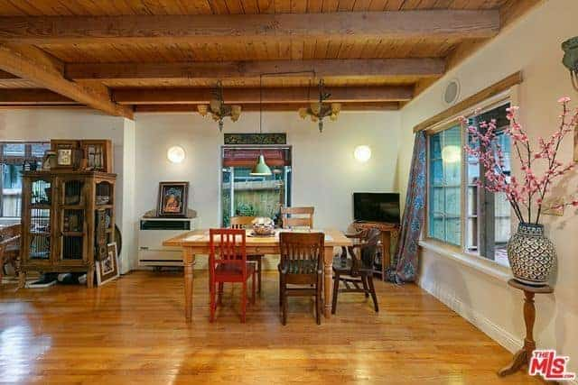 This informal Asian-style dining area has a wooden dining table that is surrounded by a variety of wooden chairs. This works well with the hardwood flooring and wooden ceiling with exposed wooden beams that hang small chandeliers over the table.