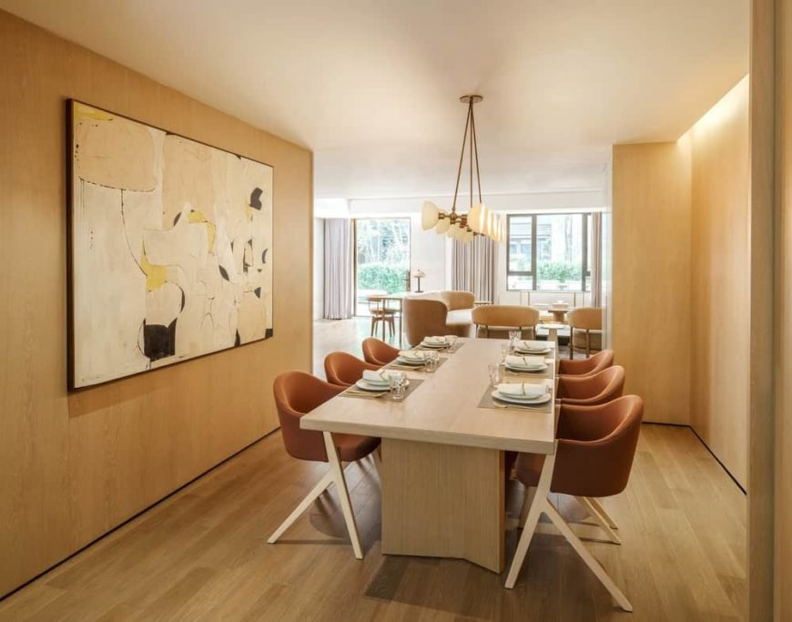 The simple wooden dining table blends with the light hardwood flooring as well as with the walls that is adorned with an abstract painting behind the brown cushioned dining chairs with the same wooden hue to its legs.