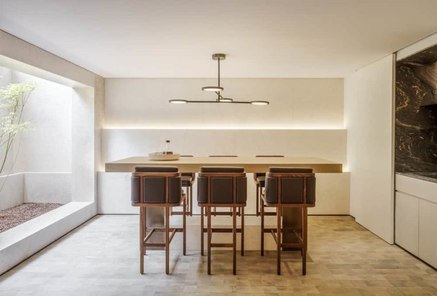 The high modern dining table is paired with modern wooden stools with gray leather cushions. These stand out against the wimple white ceiling and walls. One side of these walls is open to a small area that is fitted with soil and plants.
