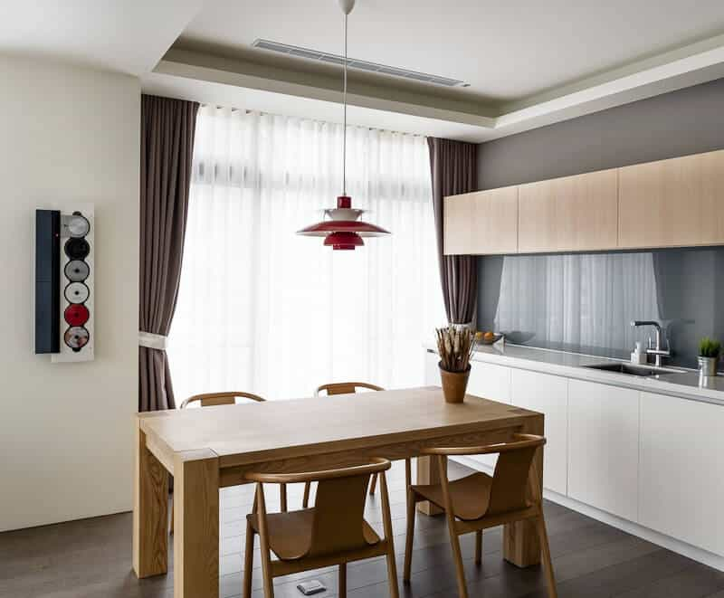 This is an informal dining area under the same white tray ceiling as that of the kitchen peninsula and its floating cabinets that match the wooden hue of the dining table and its wooden chairs that has a slightly lighter shade as the hardwood flooring.