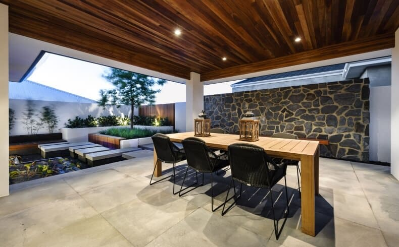 This is a wide and spacious dining room augmented by its open walls that lead to the beautiful zen garden of the backyard. Only one wall remains and it is made of textured stones of gray that complement the wooden ceiling that shines recessed lights on the wooden dining table and its black chairs.