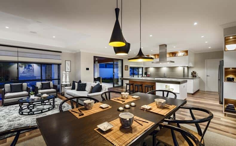 This Asian-style dining area is within the same great room as the living room area and the kitchen under the same white ceiling with recessed lights and hangs black pendant lights over the black wooden dining table paired with black wishbone chairs with woven wicker seats matching the bamboo placemats.