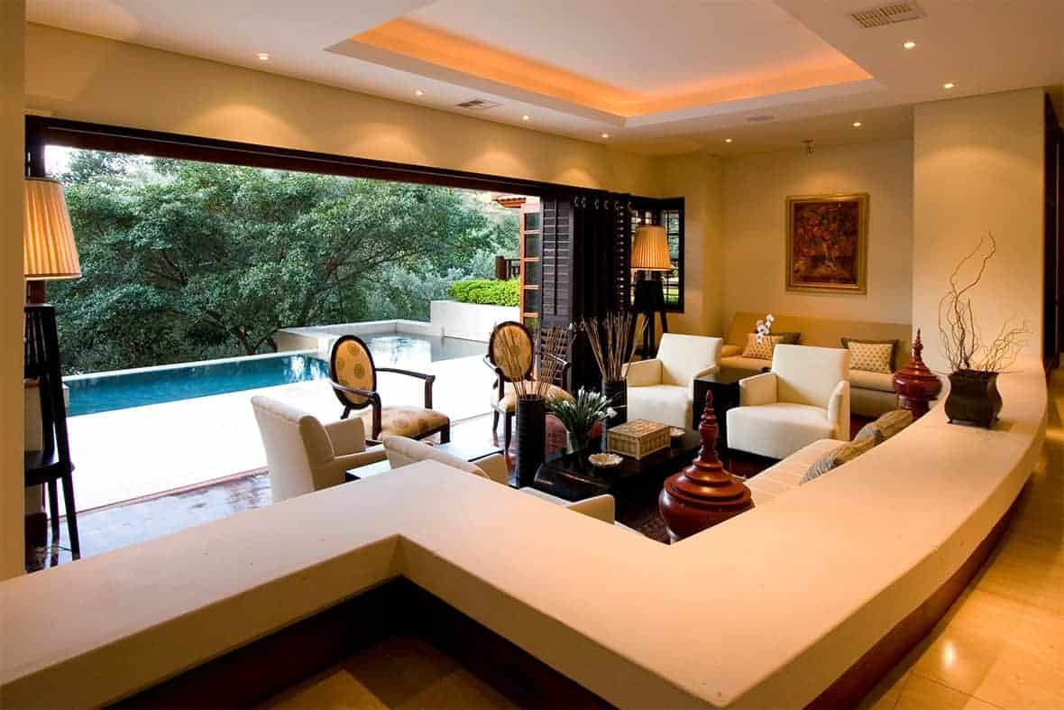The white ceiling of this living room is lit with warm yellow lights that also give warmth to the elegant elements of the sofa set and the two oval-back armchairs facing the dark coffee table. This is given a nice colorful background of a poolside view filled with <a class=
