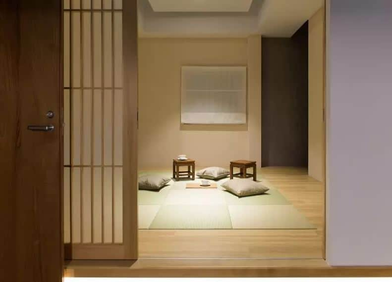 This is a traditional Japanese-style living room with beige walls and a hardwood flooring covered by a light green tatami mat matching with the green <a class=