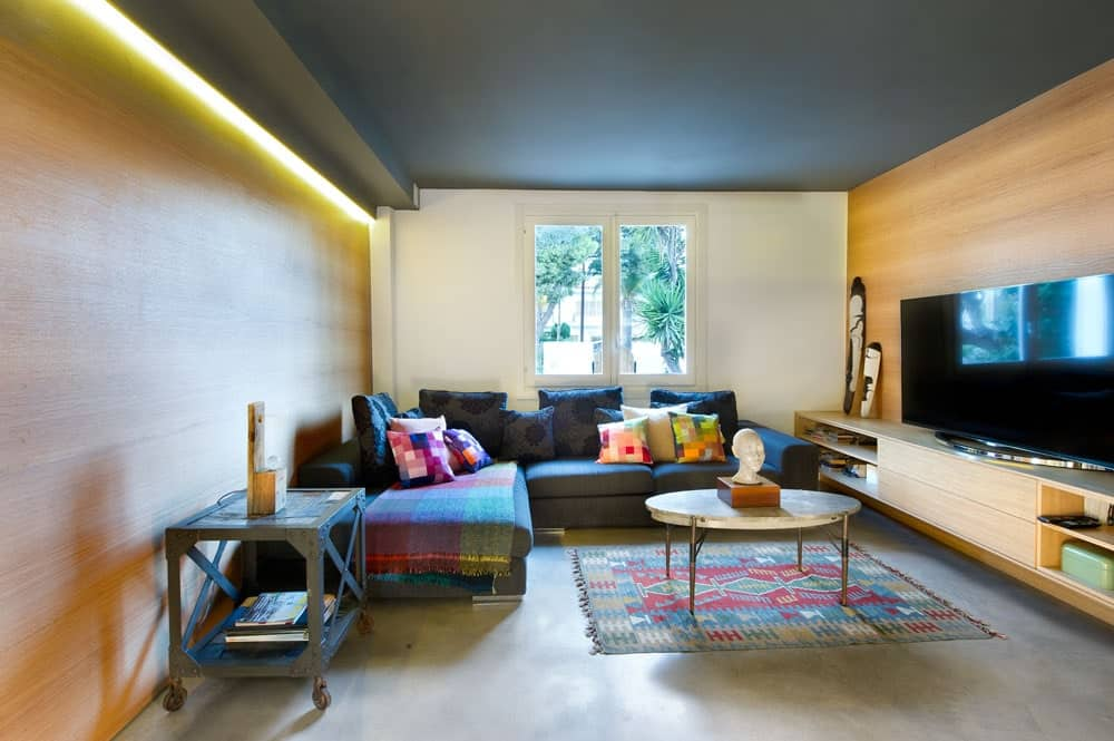 The gray ceiling matches with the gray L-shaped sofa that is complemented by the gray concrete flooring. These are then augmented by the colorful patterned area rug and the pillows on the sofa. The elements that brings them all together are the wooden walls.