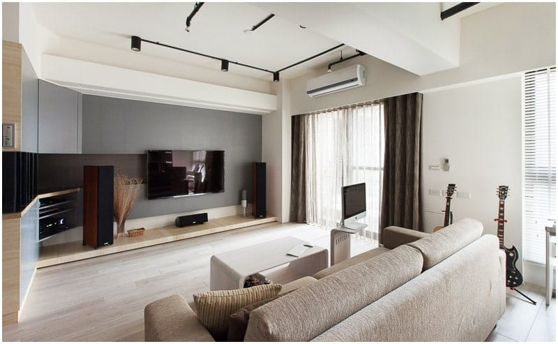 The low wooden platform under the mounted TV acts as a shelf for the sound system. This low platform matches with the light hardwood flooring that is illuminated by the natural lights coming in from the curtained windows.