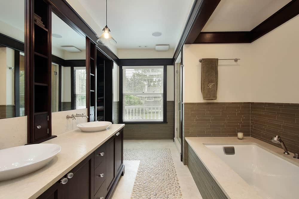 This Asian-style primary bathroom offers a single sink with two vessel sinks lighted by pendant lighting. The room offers a deep soaking tub and a walk-in shower room.
