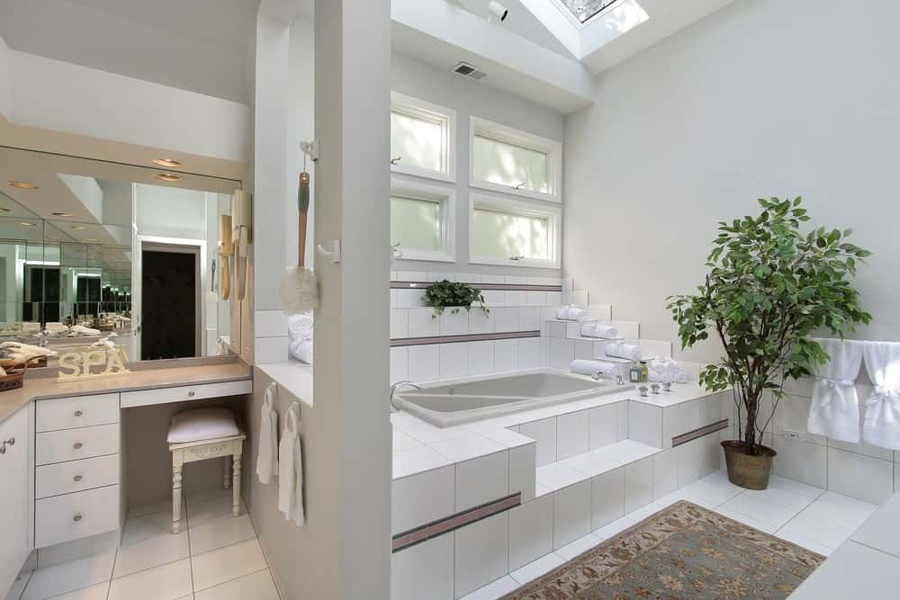 White primary bathroom with a tall ceiling with a skylight. There's a powder desk area and a deep soaking tub.