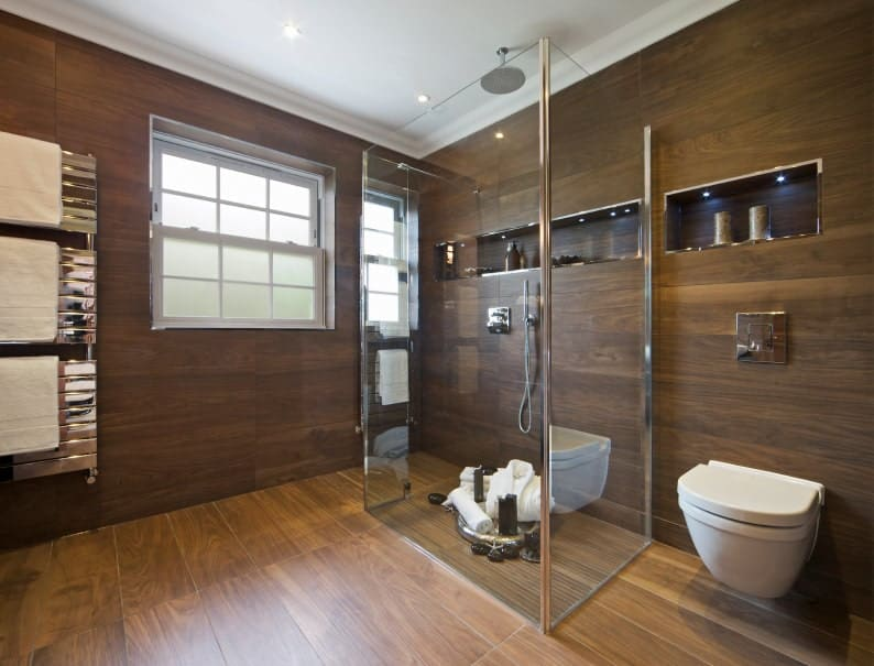 Brown Asian-style primary bathroom featuring hardwood flooring and walls. The room offers a walk-in shower.