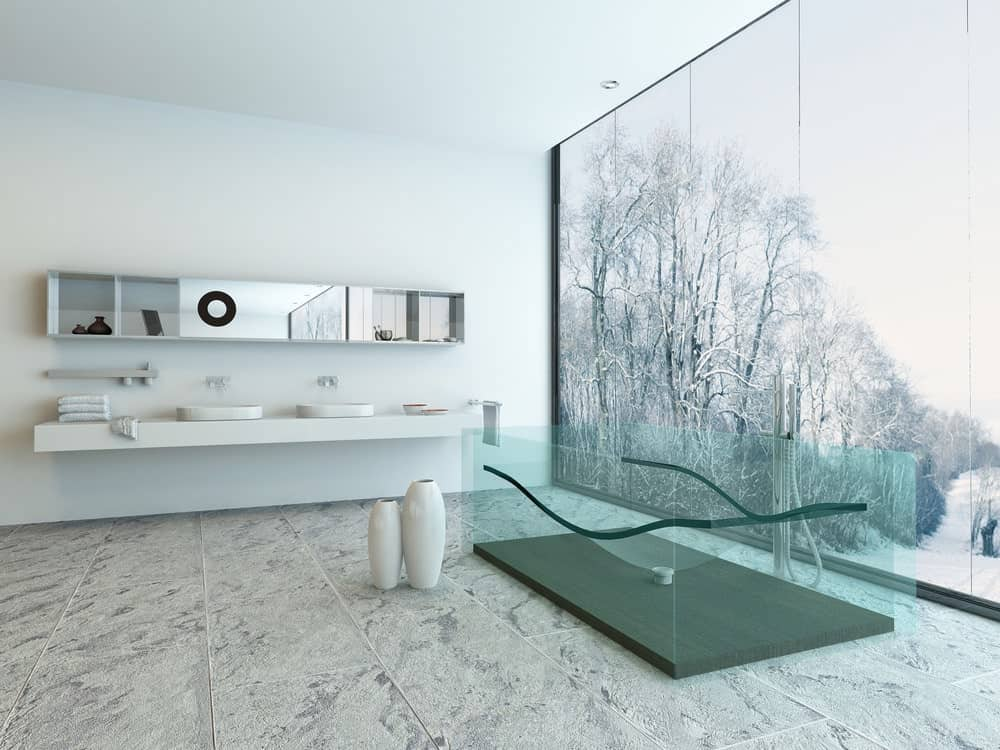 A stunning white primary bathroom featuring stylish tiles flooring and a white floating vanity with vessel sinks. The room offers a transparent glass deep soaking tub near the large glass windows overlooking the gorgeous surroundings.