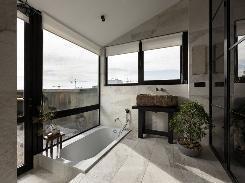This primary bathroom has a submerged soaking tub and an interesting vessel sink. There's a doorway leading to the home's balcony..