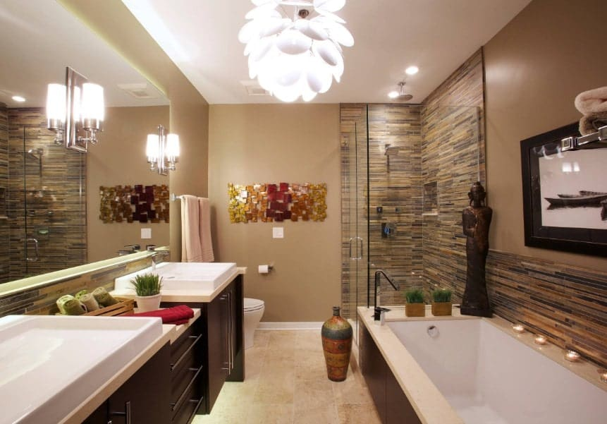 Asian-style primary bathroom featuring two vessel sinks, a walk-in shower area and a drop-in tub. The room is lighted by beautiful pendant light and wall lights.