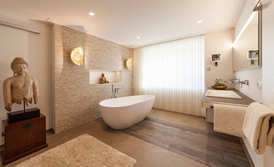 A beautiful Asian-style primary bathroom with an attractive piece of a bust decor figure along with a freestanding deep soaking tub.