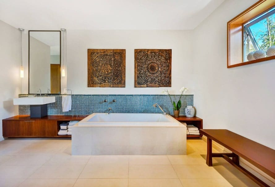 Spacious Asian-style primary bathroom with a wooden bench seating along with attractive wall decors. It offers a deep soaking tub along with a vessel sink.
