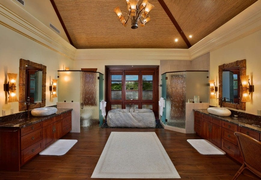 Large Asian-style primary bathroom featuring hardwood floors and a tall ceiling with a gorgeous chandelier. The room has a drop-in tub, a walk-in shower, a toilet room and two vessel sinks. The room is lighted by warm white lights.