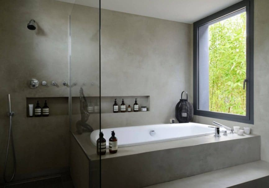 A focused shot at this Asian-style primary bathroom's walk-in shower and drop-in tub next to a window.