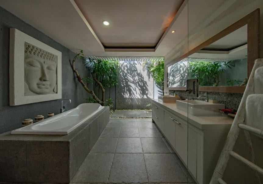 Asian-style primary bathroom featuring a long drop-in tub with a large and attractive wall decor. There's a long sink counter with two vessel sinks, along with a tray ceiling.