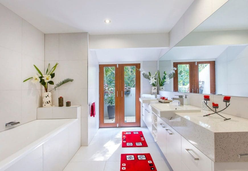 White primary bathroom with Asian-style red rugs. There's a double sink and a deep soaking tub.