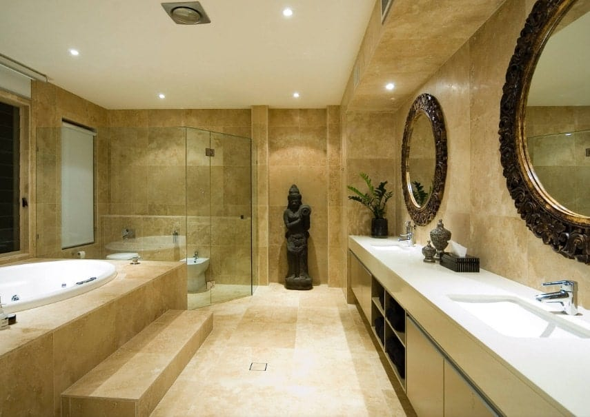 Asian-style primary bathroom boasting an eye-catching statue on the side. The room offers a single sink counter with two sinks along with a drop-in tub and a walk-in shower room.