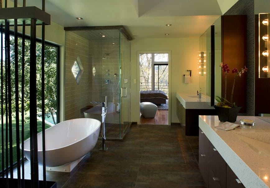 Green primary bathroom featuring a freestanding tub, a walk-in shower area and two sink counters.