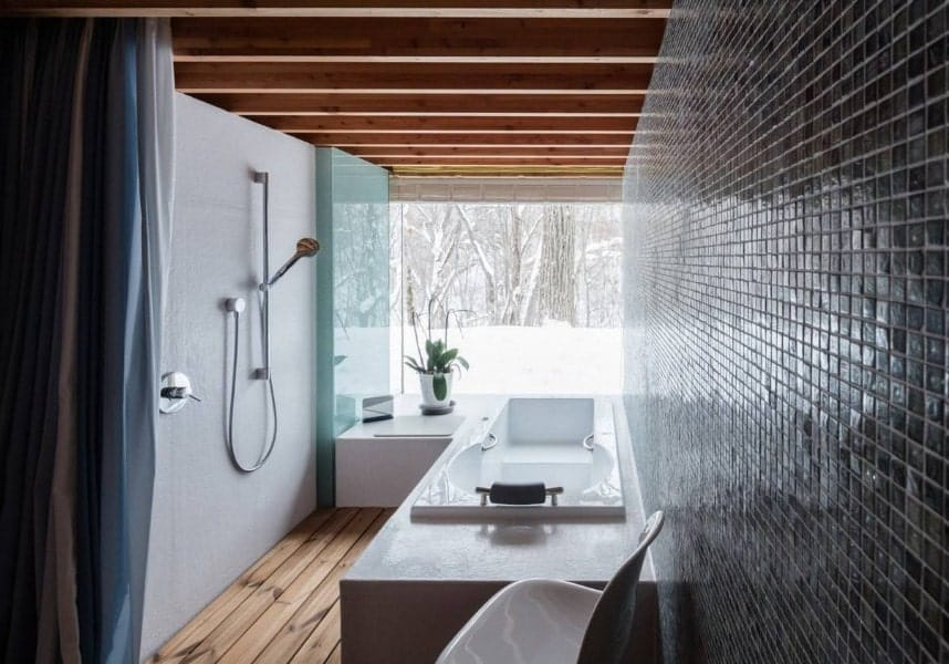 A small Asian-style bathroom featuring a drop-in tub and an open shower. The room has a ceiling with beams along with hardwood flooring.
