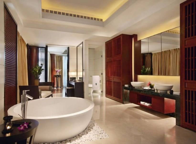Large and modern Asian-style primary bathroom with a large round freestanding tub along with a powder desk, a toilet room and a walk-in shower. There are two vessel sinks as well. The room has a tray ceiling that has gorgeous lighting.
