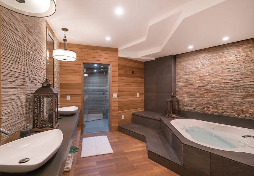 Asian-style primary bathroom with a stunning modish design. It has two vessel sinks lighted by pendant lights along with a drop-in tub under the custom ceiling with recessed lights.