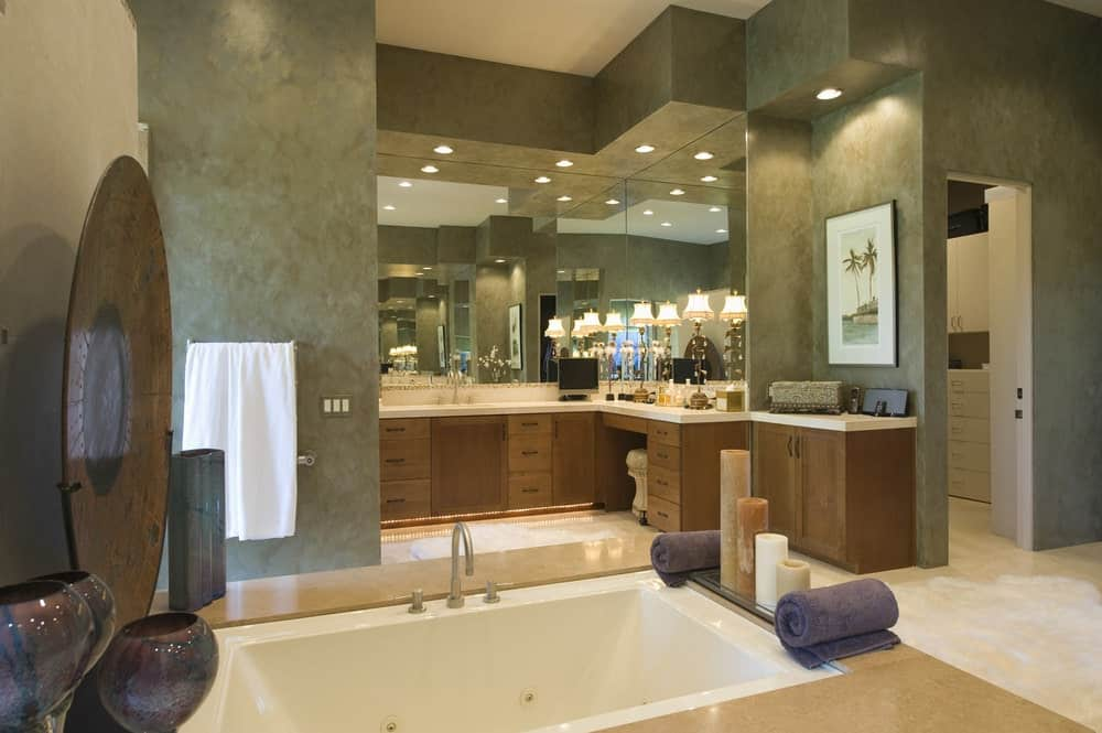 Large primary bathroom featuring a deep soaking tub along with a powder area. The room offers beautiful lighting around the room.