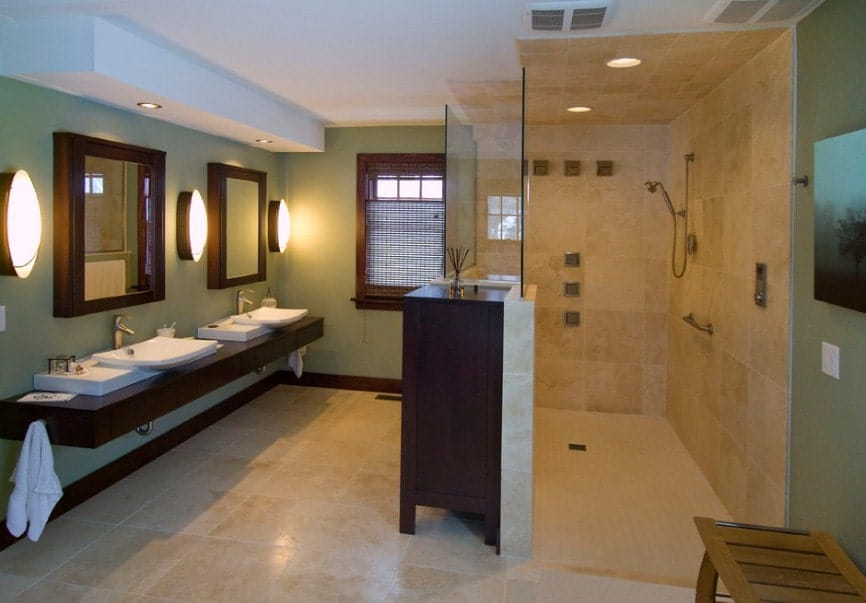 Green primary bathroom with a large walk-in shower and a floating vanity with two sinks, lighted by large round wall lights.