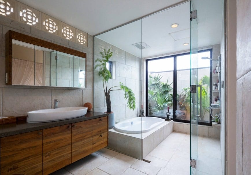 Asian-style primary bathroom featuring a walk-in shower room and tub. The room also offers a sink counter with a large vessel sink.