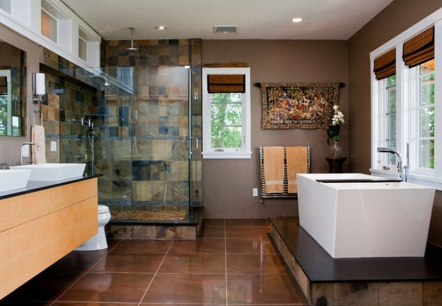 This Asian-style primary bathroom offers a walk-in shower, a freestanding tub on a nice platform and a sink counter featuring two vessel sinks.