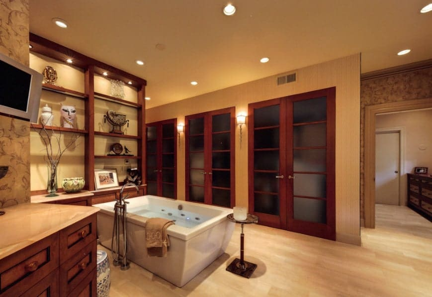 Large Asian-style primary bathroom featuring a freestanding soaking tub along with a shower room. The area has built-in shelves and cabinetry.